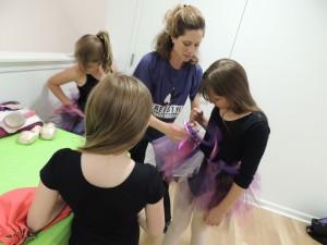 Mrs. Kristen helping prepare the ballerinas.