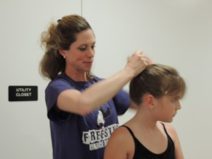 Ballet teacher Mrs. Kristen helps a student during the Freestyle Dance Academy showcase.
